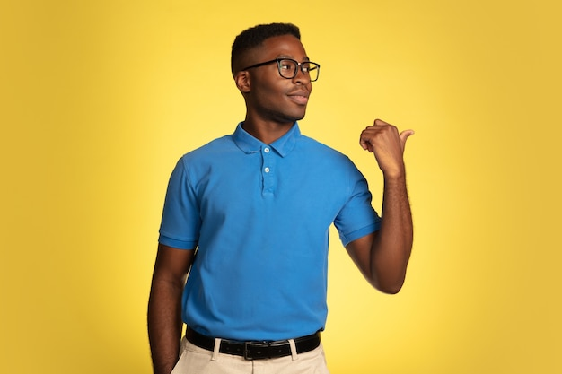ポインティング、表示。黄色のスタジオの背景、顔の表情に分離された若いアフリカ系アメリカ人の男の肖像画。コピースペースを持つ美しい男性の肖像画。人間の感情、顔の表情の概念。