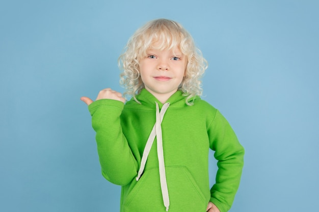 Pointing at side. portrait of beautiful caucasian little boy isolated on blue studio wall