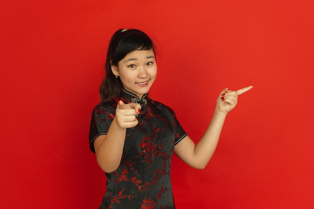 Pointing on and at side, smiling. happy chinese new year. asian young girl's portrait on red background. female model in traditional clothes looks happy. celebration, human emotions. copyspace.
