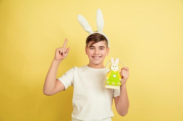 Указывая вверх. украшение. кавказский мальчик как пасхальный кролик на желтом фоне студии. поздравления с пасхой. красивая мужская модель. понятие человеческих эмоций, выражения лица, праздников. copyspace.
