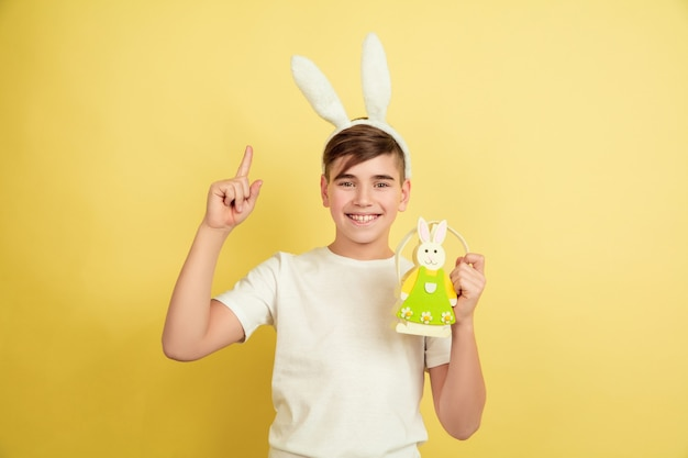 Pointing up. decorating. caucasian boy as an easter bunny on yellow studio background. happy easter greetings. beautiful male model. concept of human emotions, facial expression, holidays. copyspace.