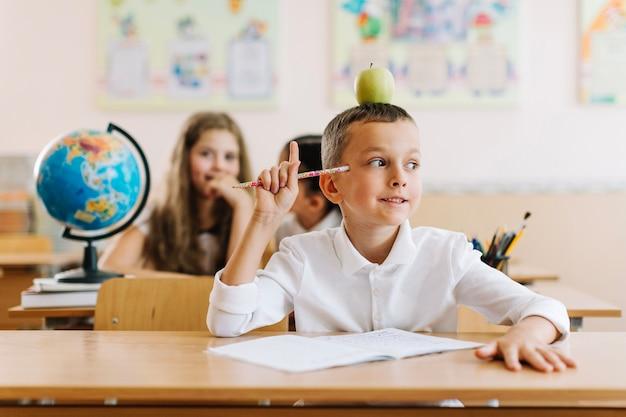 Указывая, что ребенок сидит в классе