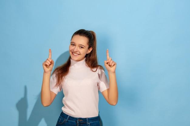 Указывая вверх, улыбаюсь. портрет кавказской девочки-подростка на синем фоне. красивая модель в повседневной одежде. понятие человеческих эмоций, выражения лица, продаж, рекламы. copyspace. выглядит мило, удивленно.