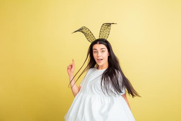 Указывая вверх, улыбаясь. кавказская женщина как пасхальный кролик на желтом фоне студии. поздравления с пасхой.
