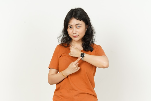 Pointing at watch of beautiful asian woman wearing orange tshirt isolated on white background