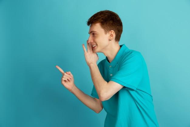가리키며 속삭이는. 파란색 벽, 단색에 고립 된 백인 젊은 남자의 현대 초상화. 아름다운 남성 모델.