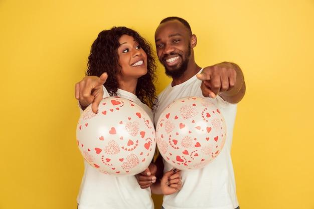 Indicando con palloncini. celebrazione di san valentino, felice coppia afro-americana isolata su sfondo giallo.