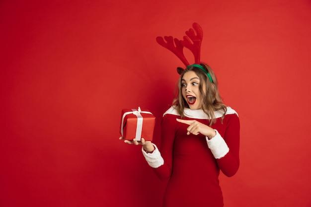 Indicando con regalo. concetto di natale, capodanno 2021, umore invernale, vacanze. . bella donna caucasica con i capelli lunghi come la confezione regalo di cattura delle renne di babbo natale.