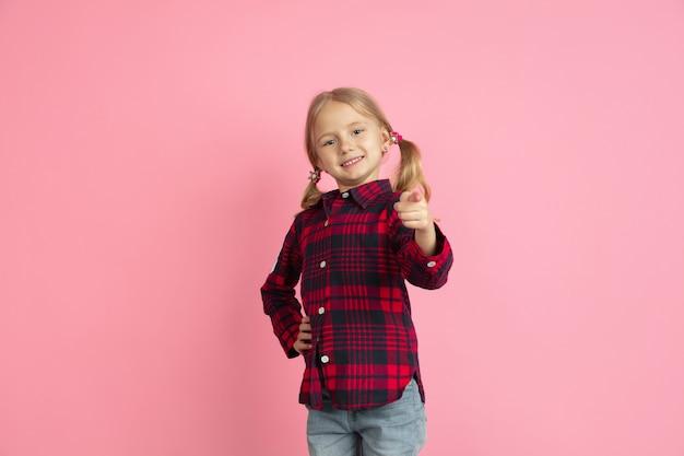 Указывая на вас, выбирая. портрет кавказской маленькой девочки на розовой стене. красивая женская модель со светлыми волосами. понятие человеческих эмоций, выражения лица, продаж, рекламы, юности, детства.