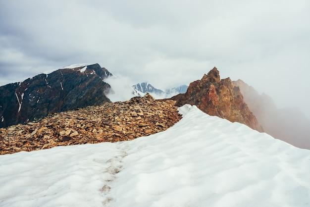 Острый скалистый пик на горе со снегом среди густых низких облаков.