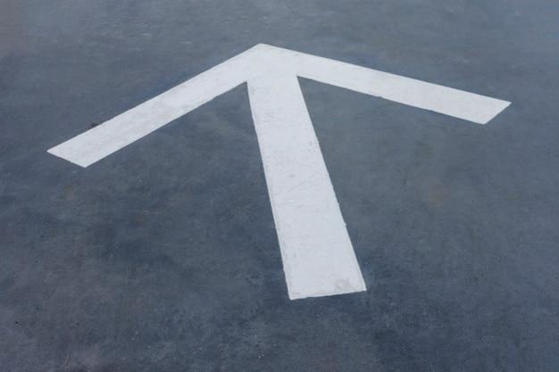 Pointy white arrow on asphalt background