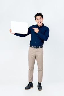 Красивый усмехаясь азиатский человек poiting рука к чистому листу бумаги