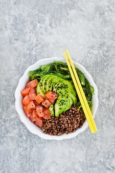 Poke bowl. ingredients: salmon, avocado, brown rice, algae.