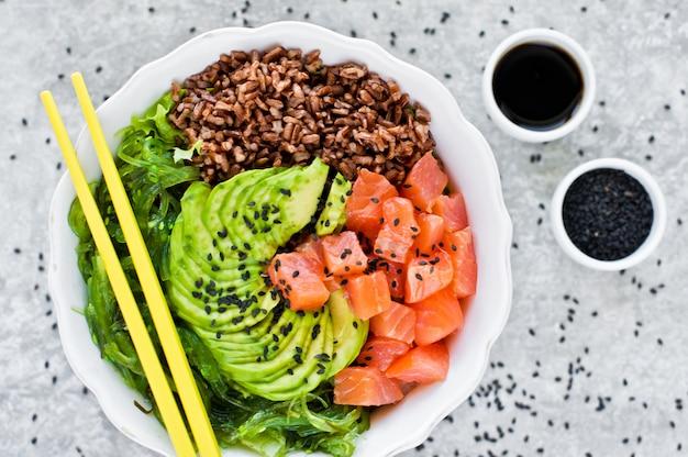 Poke bowl. ingredients: salmon, avocado, brown rice, algae.