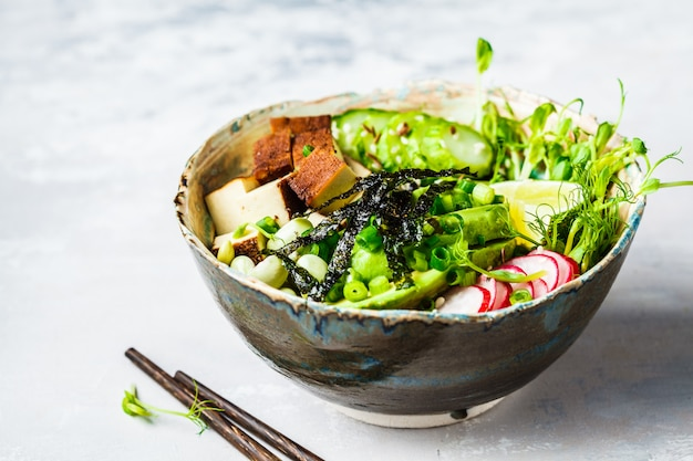 Poke bowl with avocado, black rice, smoked tofu, beans, vegetables, sprouts