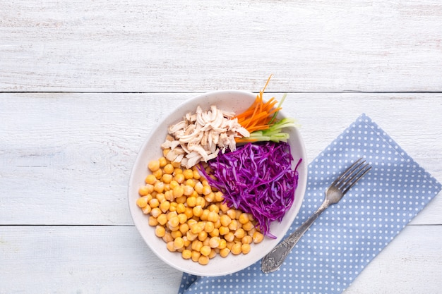 Poke bowl with chickpeas, steamed chicken, cabbage, carrots and cucumber