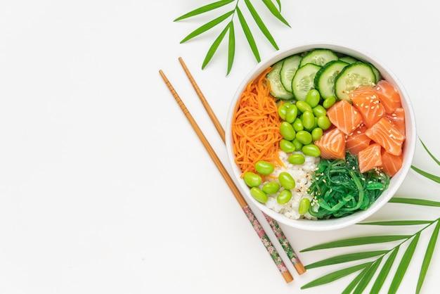 신선한 연어 쌀 chukka 샐러드 완두콩 콩 당근과 오이 그릇을 찌를 흰색 배경에 건강 식품의 그릇