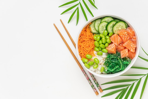 Poke bowl with fresh salmon rice chukka salad edamame beans carrots and cucumber bowl of healthy food on white background