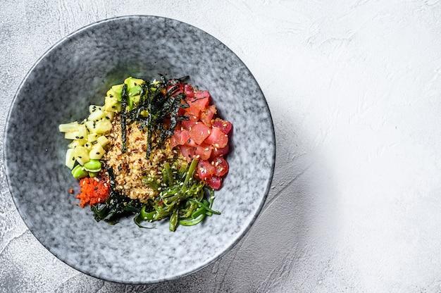 ツナの生魚と野菜のボウルを突く。ハワイアン料理。健康的な食事のコンセプトです。灰色の背景
