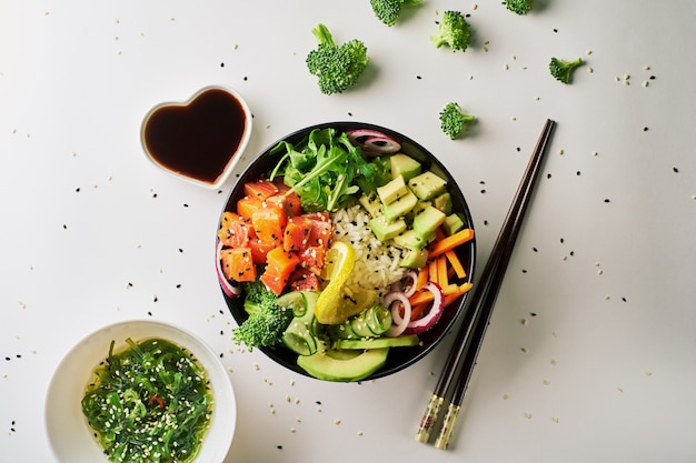 Poke bowl with salmon, avocado, chopsticks and soy sauce isolated over white background. top view