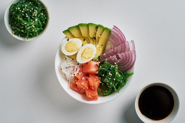 Poke bowl with salmon, avocado chuka salad sesame chuka salad soy sauce