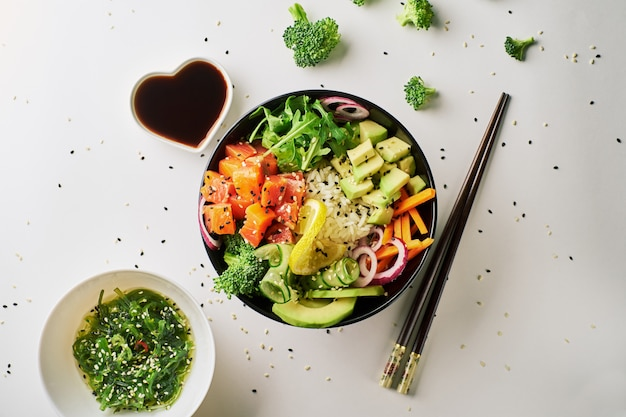 Poke bowl with salmon, avocado cucumber chopsticks and soy sauce