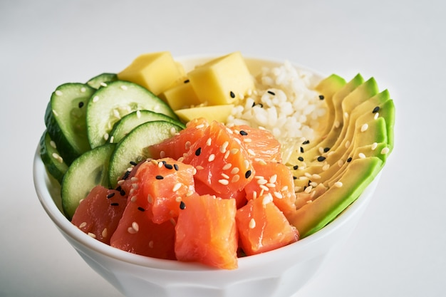 Poke bowl with salmon, avocado,  isolated on white background. close-up side view