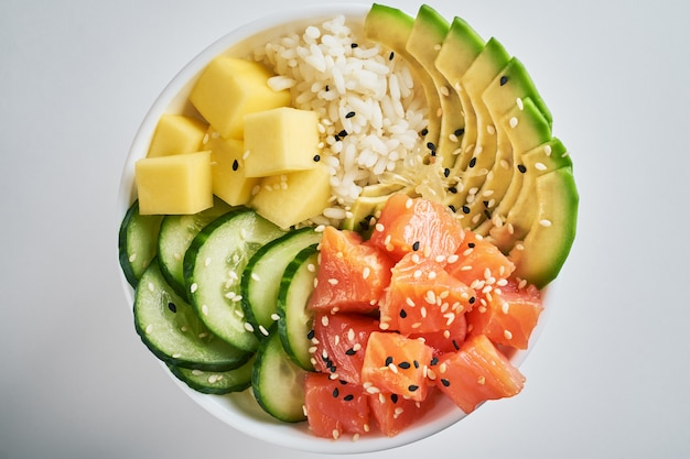 Poke bowl with salmon, avocado, mango, sesame isolated on white background.