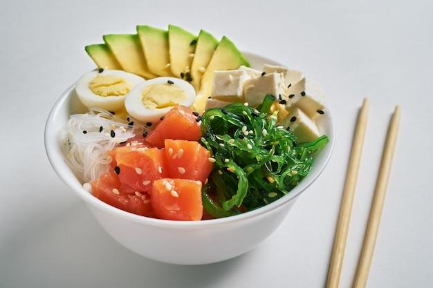 Poke bowl with salmon,avocado, rice, chuka salad, sesame with chopsticks