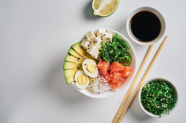 Poke bowl with salmon, avocado rice,chuka salad and soy sauce