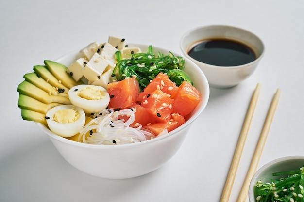 Poke bowl with salmon, avocado, rice, sesame with chopsticks soy sauce