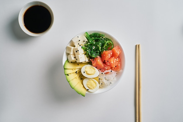 Poke bowl with salmon, avocado sesame, soy sauce