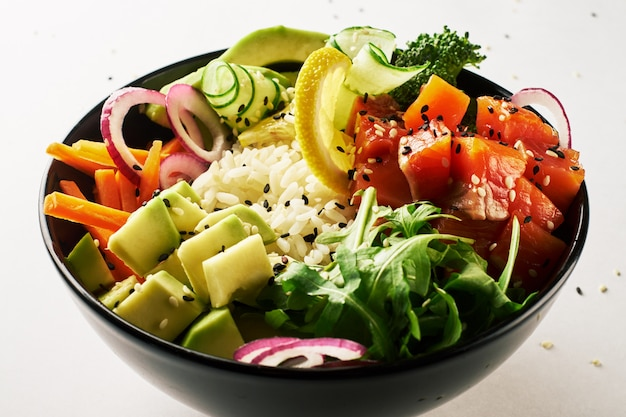 Poke bowl with salmon, avocado and sweet onions isolated over white background.
