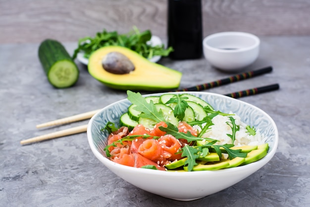 Poke bowl with salmon, cucumber, avocado, arugula and seasame seeds. ready-to-eat appetizer