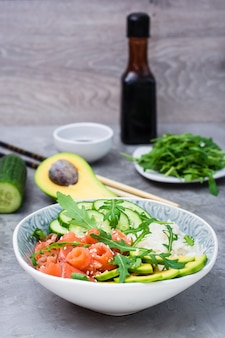 Poke bowl with salmon vegetables and sesame seeds