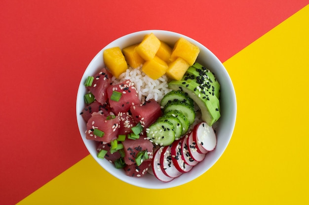 Poke bowl with tuna in the white bowl in the center of the colorful background.top view.closeup.
