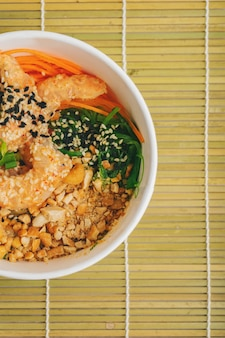 Азиатская еда с острым креветок poke bowl с рисом, водорослями и кунжутом, авокадо с палочками для еды на бамбуковой циновке над серым каменным фоном с копией пространства. здоровые морепродукты ланч-бокс.