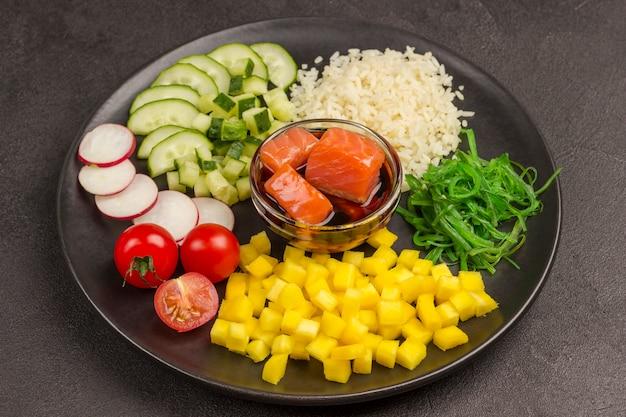 Салат poke с рисом, редисом и водорослями в черной тарелке. азиатская еда.