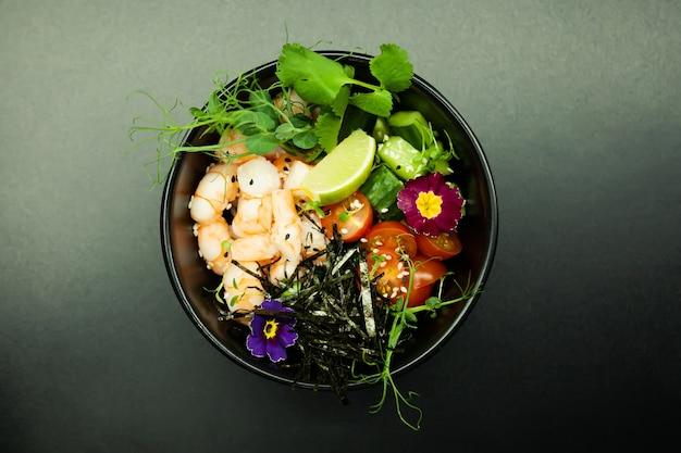 Салат poke с креветками в миске ингредиенты креветки бланшированный шпинат помидоры черри рис огурец соевый соус острый соус нори кунжут лайм кинза азиатский салат из морепродуктов концепция
