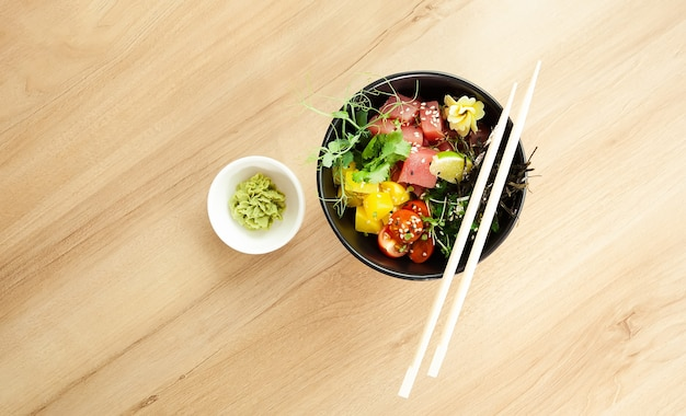 Poke salad with tuna in a bowl ingredients fresh tuna cherry tomatoes marinated seaweed rice takuan ponzu sauce teriyaki sauce nori sesame seeds lime cilantro asian seafood salad concept