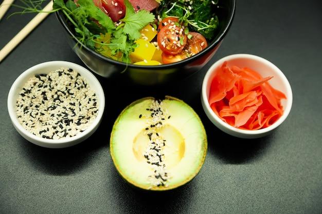 Poke salad with tuna in a bowl ingredients fresh tuna cherry tomatoes marinated seaweed rice takuan ...