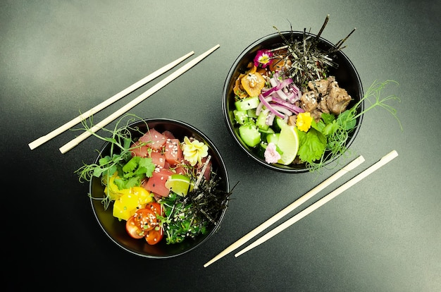 Poke salads with tuna and beef in bowls on the table two bowls of poke salad with chopsticks on a gr...