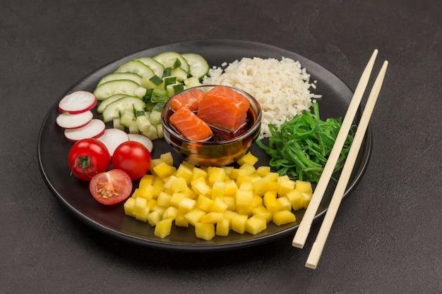 伝統的なハワイの生の赤い魚のサラダ、竹の箸を突く。有機性健康な栄養物。