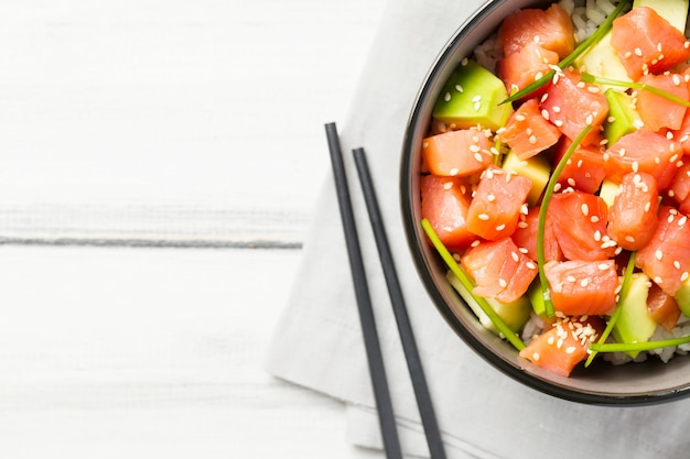 Poke with red fish and avocado decorated with green onions and sesame seeds in bowl