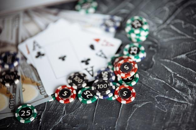 灰色の背景にポーカーカードとポーカーチップのスタック。ポーカーオンラインコンセプト。