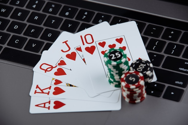 ラップトップコンピューター上のポーカーカードとポーカーチップのスタック。カジノとポーカーのオンラインコンセプト。