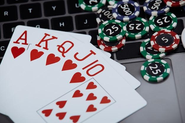 ラップトップコンピューター上のポーカーカードとポーカーチップのスタック。ポーカーオンラインコンセプト。