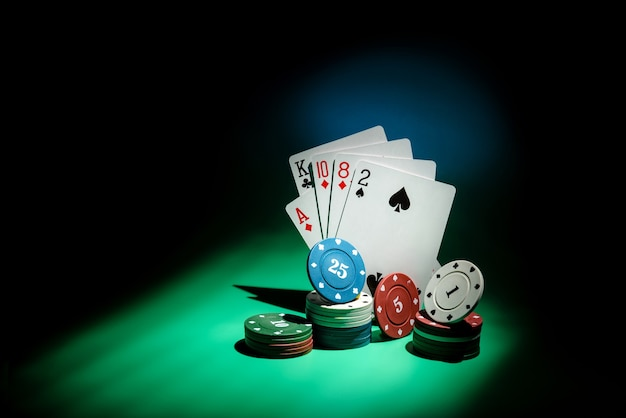 Poker cards and playing chips in a beam of light on a dark background with copy space. gambling addiction concept.