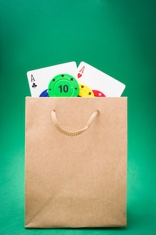 Poker cards and poker chips in bag on green background