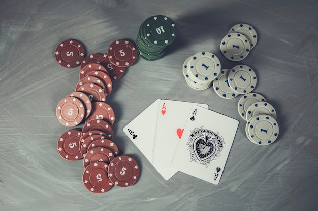 Poker cards and stacks of poker chips on a grey